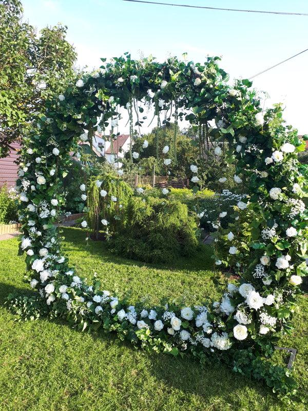 Ceremonijas arka no zaļiem augiem un baltiem ziediem