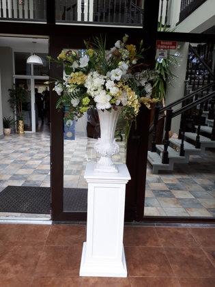 Baltu un gaišu ziedu kompozīcija baltā vāzē