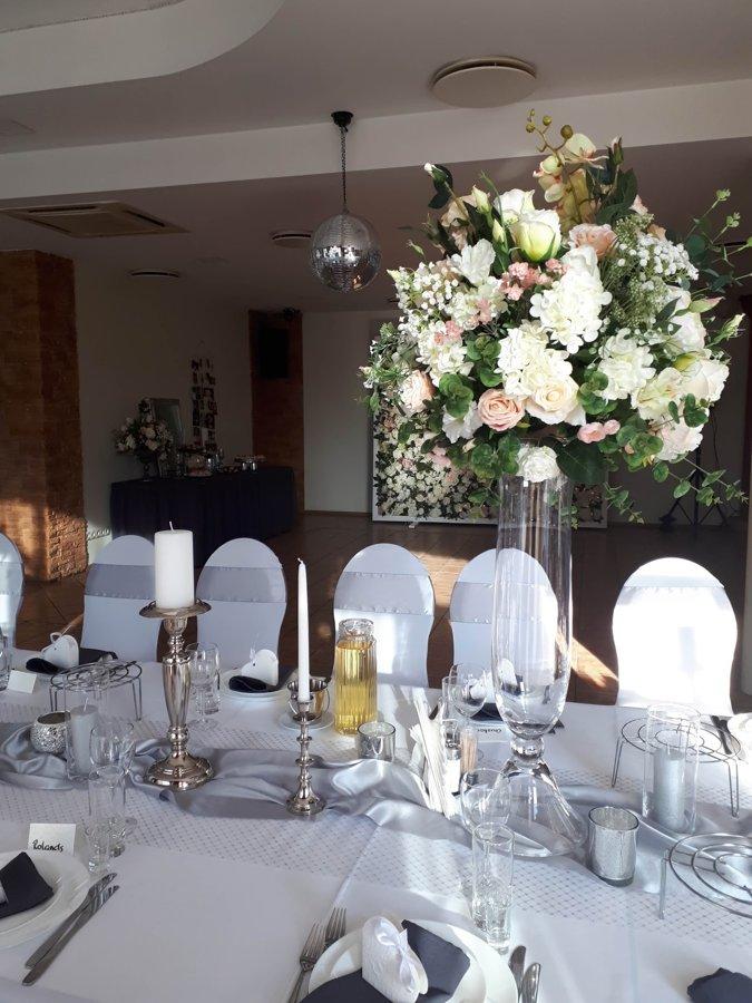Eleganti zīda ziedi augstā stikla vāzē